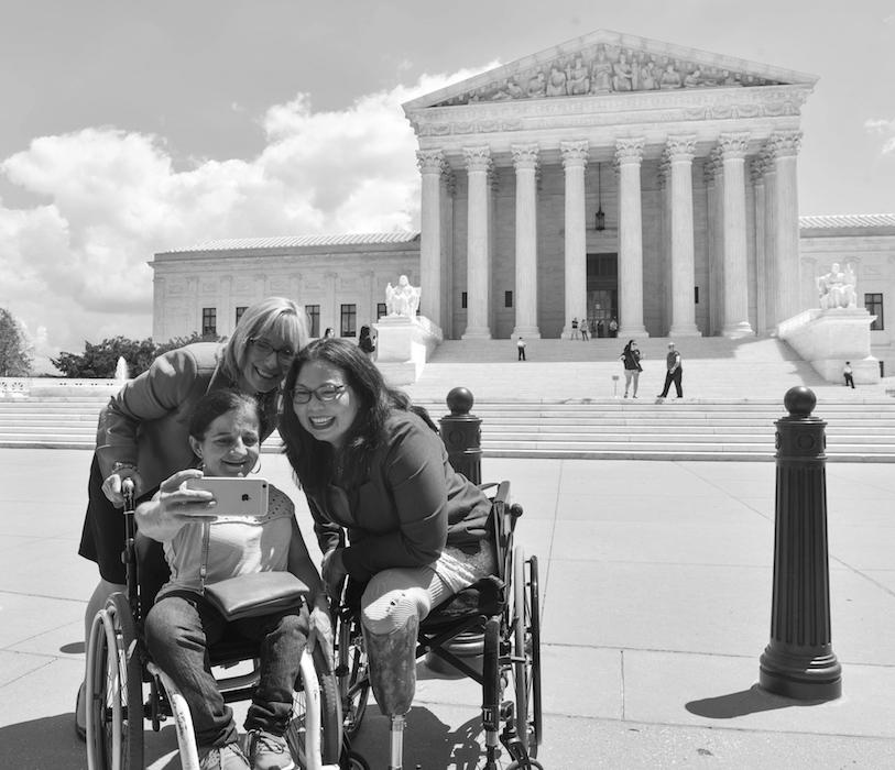Senators Maggie Hassan and Tammy Duckworth pose for a photo in front of the Supreme Court with a supporter