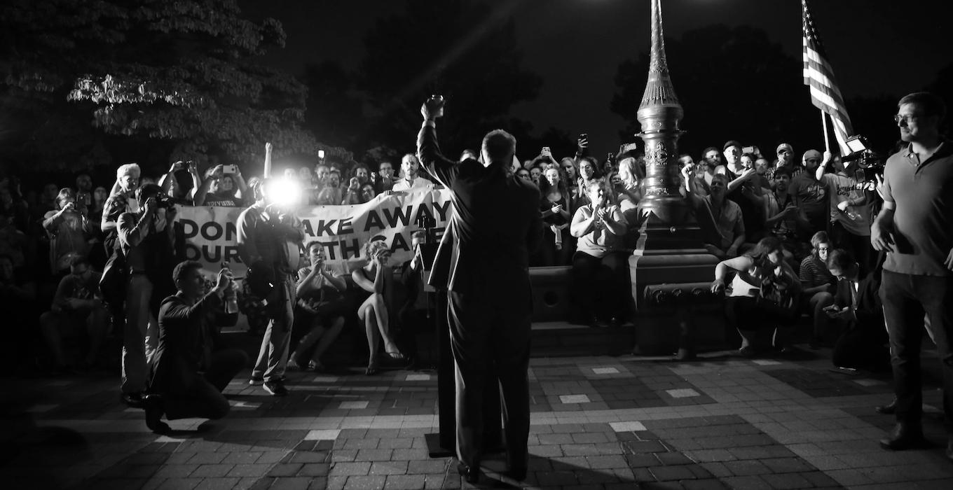 Senate Democratic Leader Chuck Schumer speaks at a healthcare rally at night